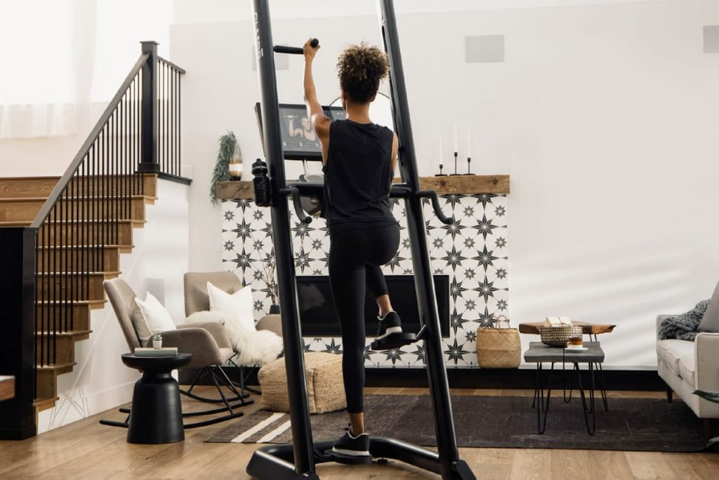 woman exercises with vertical climbing machine CLMBR in home