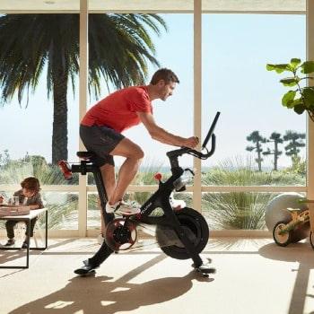 man riding peloton bike at home