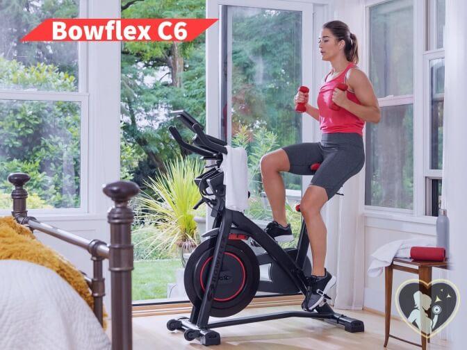 woman riding bowflexc6 and lifting dumbbells