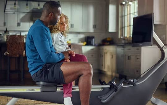 dad and daughter looking at hydrow indoor rower