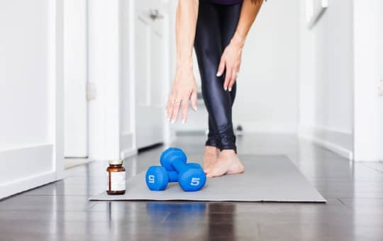 menofit bottle and dumbbells (working out and feeling great)