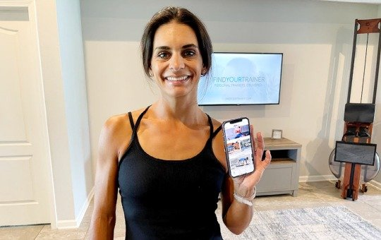 tami holding the find your trainer app at home
